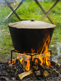 Food in a cauldron on a fire. Cooking outdoors in cast-iron cauldron. Food in a big cauldron on a fire. Cooking outdoors in cast-iron cauldron Royalty Free Stock Image