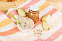 Food for children: applesauce and oatmeal on the background  light wood. Stock Photos