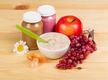 Food for children: mashed potatoes, bowl of oatmeal and fruits on background light wood. stock photos