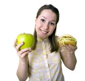 Food Choices. Woman holding an apple in one hand and a hamburger in the other.  Making a healthy food choice Stock Photography