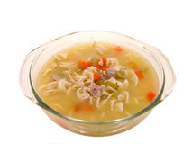 Food: Chunky Chicken Noodle Soup in Glass Cooking Dish. Chunky chicken and vegetable soup in a glass cooking dish.  Isolated on white Stock Photos