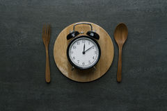 Food clock at lunch time. Healthy food concept. On wooden table Stock Photos