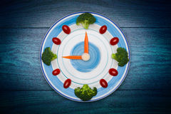 Food clock with vegetables, Healthy food concept, on wooden table Royalty Free Stock Photography