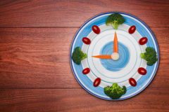 Food clock with vegetables, Healthy food concept, on wooden table Stock Photography