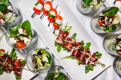 Food collage of snacks with meat and vegetables. Tapas with strawberries and cheese, salmon with pickled cucumber. Prosciutto with stock photos