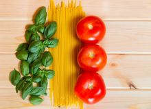 Basil, pasta and tomatoes are forming the Italian flag. Food in colors of Italian flag. Basil, pasta and tomatoes are forming the Italian flag. Italian food Royalty Free Stock Photo