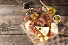 Food composition with cheese plate with cheese, dry meats, vario Stock Photos