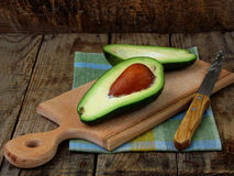 Food composition of cut in half fresh organic avocado on wooden board royalty free stock image