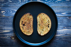 Food composition made of 2 slices of toasted bread in a black pan Stock Images
