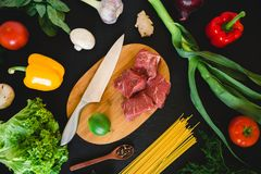 Food composition with raw meat on cooking board, knife, pasta and vegetables on dark table. Top view. Flat lay. Food composition with raw meat on cooking board Royalty Free Stock Image