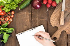 Food composition of raw vegetables, chopping board and human hand able to write something in notepad. On wooden background royalty free stock photography