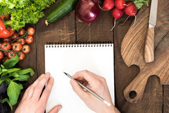 Food composition of raw vegetables, chopping board and human hand able to write something in notepad. On wooden background stock images