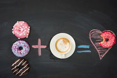 Food composition with several donuts and cup of coffee on black surface Royalty Free Stock Image