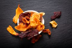 Food concept assort of vegetable chips on black slate plate royalty free stock image
