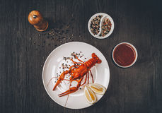 Food concept. Boiled big red fresh crawfish in white plate with lemon slices Royalty Free Stock Photos