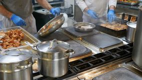 Food concept. Chef in white uniform monitors the degree of roasting and greases meat with oil in saucepan in interior of. Modern restaurant kitchen. Preparing stock footage