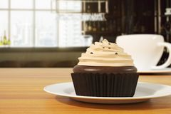 Food concept. Close up of chocolate cupcake with frosting and coffee cup on wooden table. Blurry background. Food concept. 3D Rendering Stock Photo