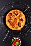 Food concept fresh baked Homemade organic Focaccia in skillet iron pan on black background with copy space royalty free stock photo