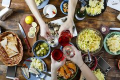 Food Concept Friends at a dinner table with different food. Easter, Christmas, Birthday, Thanksgiving. Joint toast and blow with a royalty free stock photos