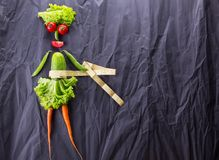 A food concept of the girl with vegetables on black paper background. Weight loss and healthy lifestyle. With space for text stock photography