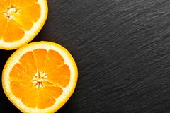 Food concept organic Orange or pomelo fruit cut haft on black slate stone board stock photography