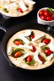 Food concept rising dough for vegan Homemade organic Focaccia in skillet iron pan on black background with copy space royalty free stock image