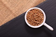 Food concept Spices coriander seeds on black slate stone and sackclot Stock Image