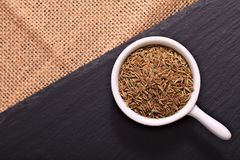 Food concept Spices Cumin seeds on black slate stone and sackclot Stock Images