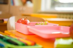 Food container. With apple and salad in classroom Royalty Free Stock Images