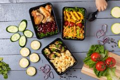 Food container boxes and girl hand holds spoon, raw vegetables, zuchini and eggplants, carrot and onion, place for text in center royalty free stock image