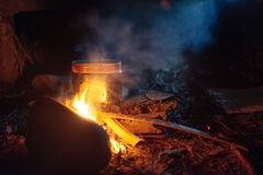 Food is cooked in pot over a campfire at night Royalty Free Stock Photography