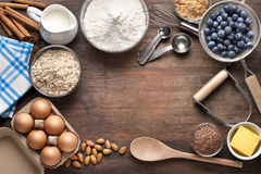 Food Cooking Baking Background. Various food ingredients and cooking utensils on a wood background with a clear center from overhead Stock Image