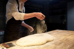 Chef or baker making bread dough at bakery. Food cooking, baking and people concept - chef or baker making bread and pouring flour to dough at bakery Stock Image