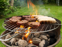 Food cooking on barbecue. Hamburgers and sausages cooking on barbecue in garden Stock Images