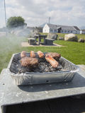 Food cooking on barbecue. Meat cooking on a disposable bbq Stock Image