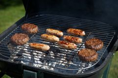 Food Cooking on a Barbeque. Sausages and Beef burgers sizzle on a charcoal Barbeque. Bright Sunlight lights this typical Summer afternoon scene Royalty Free Stock Photo