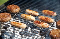 Food Cooking on a Barbeque. Sausages and Beef burgers sizzle on a charcoal Barbeque. Bright Sunlight lights this typical Summer afternoon scene royalty free stock photography
