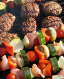 Food cooking on a barbeque. Burgers and kebabs sizzle on a barbeque stock photos