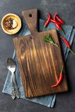 Food cooking concept. Vintage wooden kitchen board, cutlery and red pepper over napkin. On dark stone background. Top view stock image