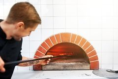 Man with peel placing pizza to oven at pizzeria. Food cooking, culinary and people concept - cook or baker with peel placing pizza to oven at pizzeria Stock Image