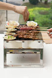 Food cooking on grill. Closeup of meat and food being cooked on an outdoor barbecue grill Stock Images