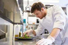 Happy male chef cooking food at restaurant kitchen. Food cooking, profession and people concept - happy male chef cook making vegetable salad at restaurant Stock Photo