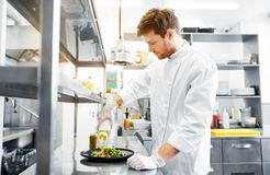 Happy male chef cooking food at restaurant kitchen stock image