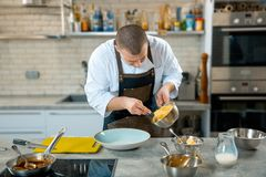 Food cooking, profession and people concept - male chef cook serving plate of polenta and veal tongues with sauce at restaurant ki stock photos