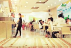 Food court blurred. Defocused or blurred photo of food court montage with wood table top use for background stock photography