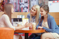 Food court in the shopping mall. Warm friendly talk by the cocktail. Three charming young ladies having an exciting conversation sitting at the cafe in shopping Royalty Free Stock Images