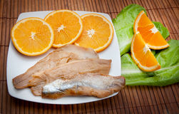 Food cousine composition ingredient for eating fish and orange. Stockfish fish composition, salad and orange Stock Photography