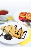 Food of Crepes, cheesecakes with berry sause and cup of tee. Stock Photo
