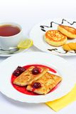 Food of Crepes, cheesecakes with berry sause and cup of tee. Stock Images