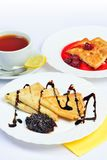 Food of Crepes, cheesecakes with berry sause and cup of tee. Royalty Free Stock Photos